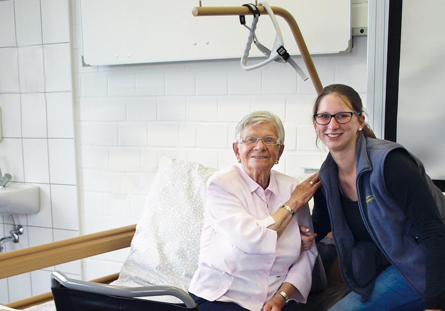 Pflegerin mit älterer Dame am Bett