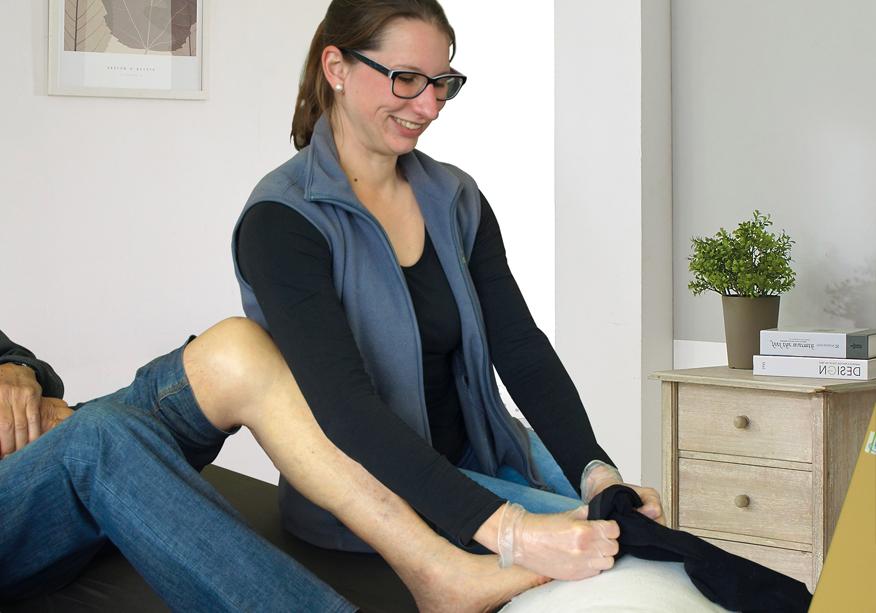 Pflegerin zieht Senior eine Socke an